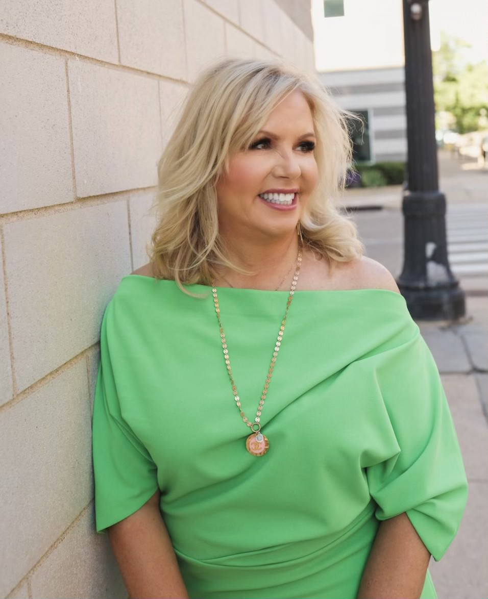 Image of Cyndi Garza in a bright green dress smiling and leaning against a building